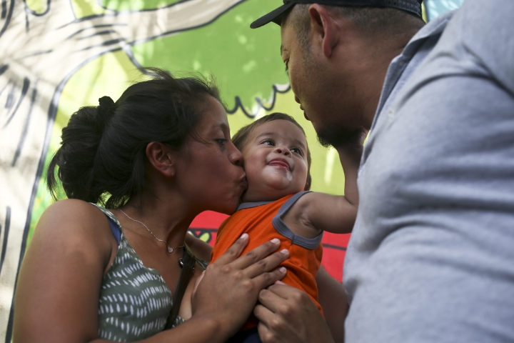 Adalicia Montecino kisses her year-old son Johan Bueso Montecinos, who became a poster child for the U.S. policy of separating immigrants and their children, as Johan touches his father Rolando Bueso Castillo's face, in San Pedro Sula, Honduras, Friday, 20, 2018. Johan Bueso Montecinos arrived in San Pedro Sula and was reunited with his parents on a government bus. Captured by Border Patrol agents in March, Johan's father was deported and the then 10-month-old remained at an Arizona shelter. (AP Photo/Esteban Felix)