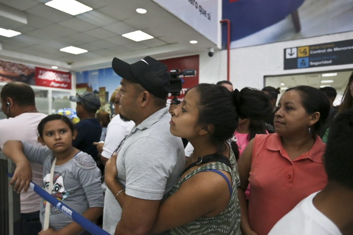 Rolando Bueso Castillo and his wife Adalicia Montecinos wait for the arrival of their year-old son who became a poster child for the U.S. policy of separating immigrants and their children, at the airport in San Pedro de Sula, Honduras, Friday, 20, 2018. Johan Bueso Montecinos arrived in San Pedro Sula and was reunited with his parents on a government bus. Captured by Border Patrol agents in March, Johan's father was deported — and the then 10-month-old remained at an Arizona shelter. (AP Photo/Esteban Felix)