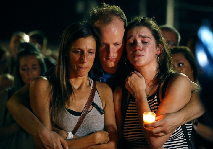 Mallory Cunningham, left, Santino Tomasetti, center, and Aubrey Reece attend a candlelight vigil in the parking lot of Ride the Ducks Friday, July 20, 2018, in Branson, Mo. One of the company's duck boats capsized Thursday night resulting in over a dozen deaths on Table Rock Lake. (AP Photo/Charlie Riedel)
