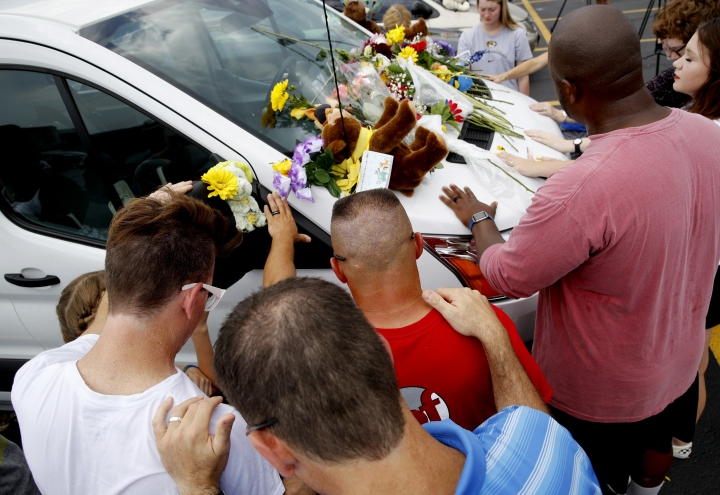 People pray around a van believed to belong to victims of a duck boat accident in the parking lot of the business running the boat tours Friday, July 20, 2018 in Branson, Mo. The country-and-western tourist town of Branson, Missouri, mourned Friday for more than a dozen sightseers who were killed when a duck boat capsized and sank in stormy weather in the deadliest such accident in almost two decades. (AP Photo/Charlie Riedel)