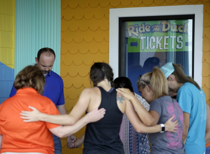 People pray outside Ride the Ducks, an amphibious tour operator involved in last night's duck boat accident on Table Rock Lake, Friday, July 20, 2018 in Branson, Mo. The country-and-western tourist town of Branson, Missouri, mourned Friday for more than a dozen sightseers who were killed when a duck boat capsized and sank in stormy weather in the deadliest such accident in almost two decades. (AP Photo/Charlie Riedel)