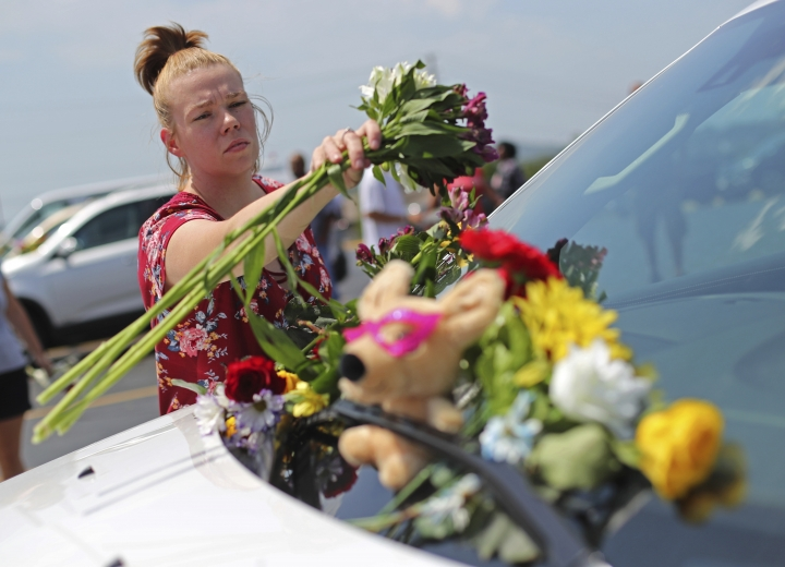 Jasmine Burkhardt leaves flowers on a car believed to belong to a victim of a last night's duck boat accident, Friday, July 20, 2018 in Branson, Mo. The country-and-western tourist town of Branson, Missouri, mourned Friday for more than a dozen sightseers who were killed when a duck boat capsized and sank in stormy weather in the deadliest such accident in almost two decades. (AP Photo/Charlie Riedel)