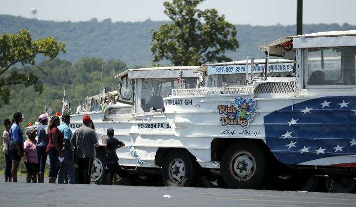 People view a row of idled duck boats in the parking lot of Ride the Ducks Saturday, July 21, 2018 in Branson, Mo. One of the company's duck boats capsized Thursday night resulting in several deaths on Table Rock Lake. (AP Photo/Charlie Riedel)