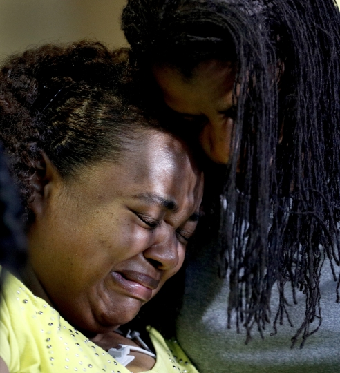 Duck boat accident survivor Tia Coleman is comforted by her sister Leeta Bigbee after speaking to the media at Cox Medical Center Branson Saturday, July 21, 2018, in Branson, Mo. Coleman lost nine family members in the accident Thursday on Table Rock Lake which left over a dozen people dead. (AP Photo/Charlie Riedel)