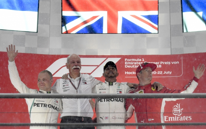 Mercedes driver Lewis Hamilton of Britain, second right, celebrates on the podium with second placed Mercedes driver Valtteri Bottas of Finland, left, Chairman of the Board of Management of Daimler AG Dieter Zetsche, second left, and third placed Ferrari driver Kimi Raikkonen of Finland after winning the German Formula One Grand Prix at the Hockenheimring racetrack in Hockenheim, Germany, Sunday, July 22, 2018. (AP Photo/Jens Meyer)