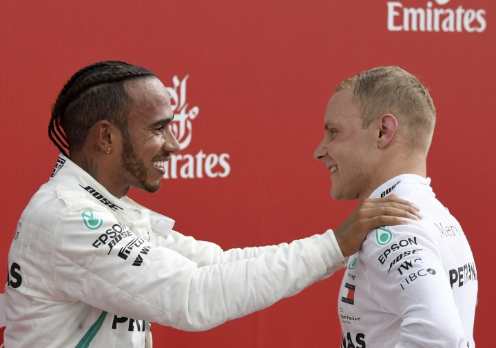 Mercedes driver Lewis Hamilton of Britain, left, celebrates with second placed Mercedes driver Valtteri Bottas of Finland after winning the German Formula One Grand Prix at the Hockenheimring racetrack in Hockenheim, Germany, Sunday, July 22, 2018. (AP Photo/Jens Meyer)