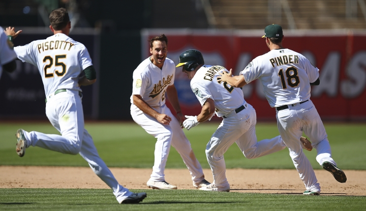 Oakland Athletics' Matt Chapman, second from right, celebrates with teammates Stephen Piscotty (25) and Chad Pinder (18) and Matt Olson, second from left, after making the winning hit against the San Francisco Giants in the 10th inning of a baseball game Sunday, July 22, 2018, in Oakland, Calif. (AP Photo/Ben Margot)