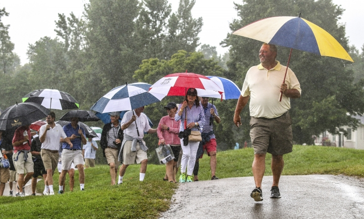 Bill Rogers, right, walks in the rain along the cart path adjacent to hole 9 with other spectators on Sunday, July 22, 2018 during the final round of the PGA Tour Barbasol Championships at Keene Trace Golf Club. (Greg Eans/The Messenger-Inquirer via AP)