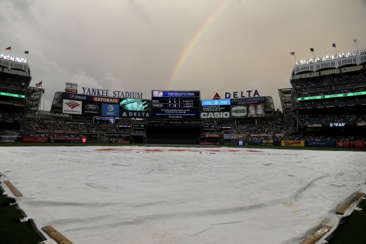 A rainbow appears over Yankee Stadium while the tarp remains on the field before a baseball game between the New York Yankees and the New York Mets, Sunday, July 22, 2018, in New York. (AP Photo/Seth Wenig)