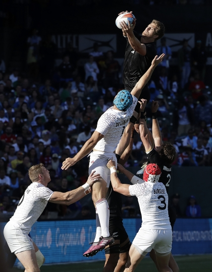 New Zealand's Scott Curry, top, reaches for the ball over England's Richard de Carpentier, center, during the Rugby Sevens World Cup championship final in San Francisco, Sunday, July 22, 2018. New Zealand won 33-12. (AP Photo/Jeff Chiu)