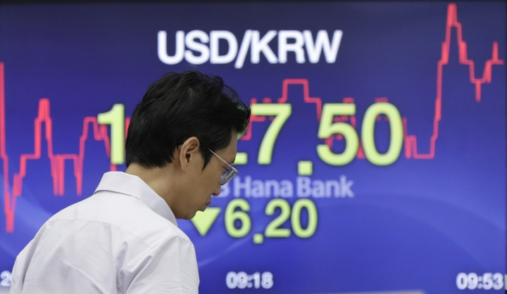 A currency trader walks by the screen showing the foreign exchange rate between U.S. dollar and South Korean won at the foreign exchange dealing room in Seoul, South Korea, Monday, July 23, 2018. Asian markets were mostly lower on Monday as concerns over trade tensions moved to the forefront at the meeting this weekend of the Group of 20 industrial nations. (AP Photo/Lee Jin-man)