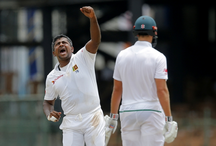 Sri Lanka's Rangana Herath, left, celebrates the dismissal of South Africa's Temba Bavuma during the fourth day's play of their second test cricket match in Colombo, Sri Lanka, Monday, July 23, 2018. (AP Photo/Eranga Jayawardena)