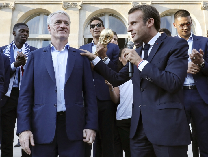 French President Emmanuel Macron, right, speaks next to France coach Didier Deschamps as he welcomes players during an official reception at the Elysee Presidential Palace in Paris, Monday, July 16, 2018. France is readying to welcome home the national soccer team for a parade down the Champs-Elysees, where tens of thousands thronged after the team's 4-2 victory over Croatia Sunday. (Ludovic Marin/Pool Photo via AP)