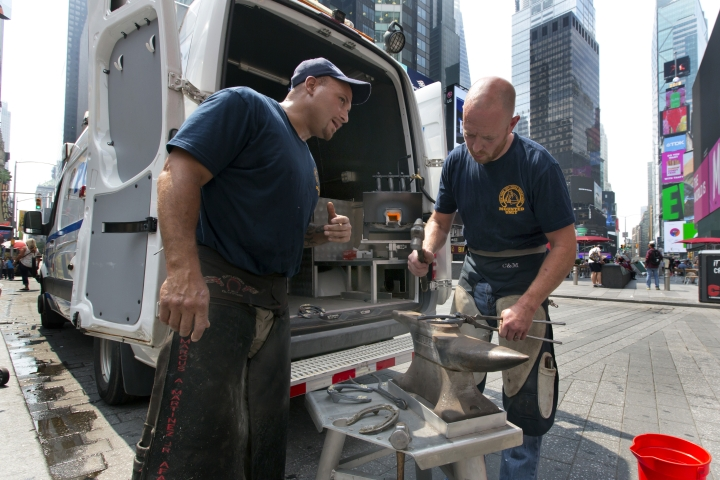 In this Tuesday, July 17, 2018 photo, New York City Police Department farriers Marcus Martinez Jr., left, and Thomas Nolan confer at their mobile workshop, as they prepare to shoe a department horse in New York's Times Square. The NYPD has two such mobile horseshoe units stocked with all manner of anvils, hammers, nippers and pullers that have been the tools of the equine hoof trade for centuries. (AP Photo/Richard Drew)