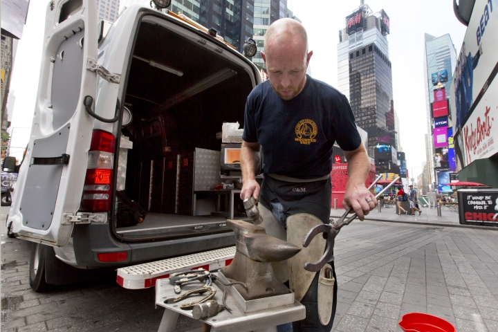 In this Tuesday, July 17, 2018 photo, New York City Police Department farrier Thomas Nolan uses a hammer and anvil as he shapes a horseshoe, while working from a mobile unit in New York's Times Square. When one of the New York Police Department's horses loses a metal shoe, or they just wear out on the gritty city streets, a blacksmith shop on wheels rushes to the rescue, equipped with a 2,850-degree furnace and trained farriers who can make the fix on the spot. (AP Photo/Richard Drew)
