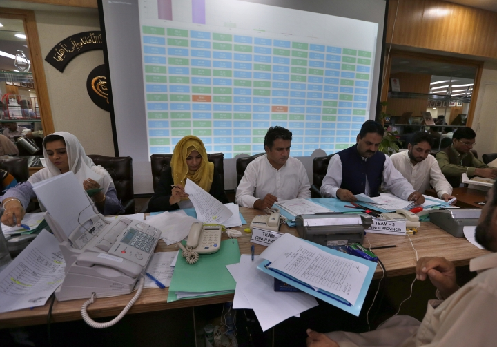 Pakistan Election Commission staff compile official results of the parliamentary elections in Islamabad, Thursday, July 26, 2018. Pakistan's former cricket star Imran Khan and his party were maintaining a commanding lead Thursday amid slow and tedious counting of ballots from a historic election. Election officials said an official count confirming Pakistan's next government was expected later in the evening. (AP Photo/Anjum Naveed)