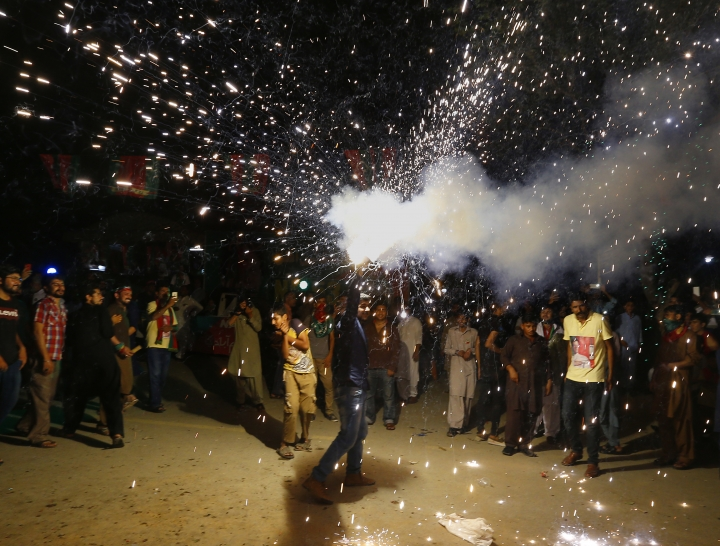 A supporter of Pakistani politician Imran Khan, chief of Pakistan Tehreek-e-Insaf party, releases fireworks to celebrate projected unofficial results announced by television channels indicating their candidates' success in the parliamentary elections in Islamabad, Pakistan, Thursday, July 26, 2018. (AP Photo/Anjum Naveed)