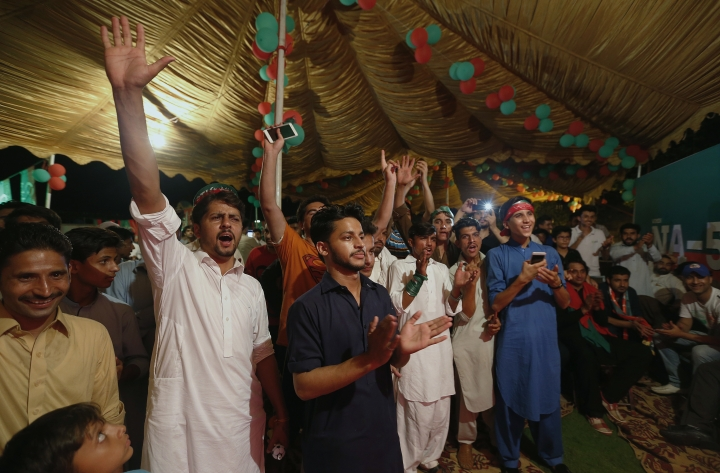 Supporters of Pakistani politician Imran Khan, chief of Pakistan Tehreek-e-Insaf party, celebrate projected unofficial results announced by television channels indicating their candidates' success in the parliamentary elections in Islamabad, Pakistan, Wednesday, Thursday, July 26, 2018. (AP Photo/Anjum Naveed)