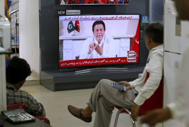 "People listen the speech of Pakistani politician Imran Khan, chief of Pakistan Tehreek-e-Insaf party, telecasting on news channels at a shop in Islamabad, Pakistan, Thursday, July 26, 2018. Khan declared victory Thursday for his party in the country's general elections, promising a ""new"" Pakistan following a vote that was marred by allegations of fraud and militant violence. (AP Photo/Anjum Naveed)"