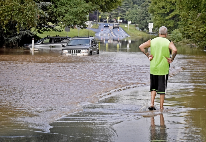 Louis Binino, of Mount Joy, Pa., looks at his SUV, far left, that became stranded in high water along Rt 772 in Mount Joy, Pa., Wednesday, July 25, 2018. Binino waded though the water to safety after climbing out the window of the vehicle. Days of drenching rains are closing roads, sending creeks and streams over their banks and causing businesses and to shut down in central Pennsylvania. (Blaine Shahan/LNP via AP)