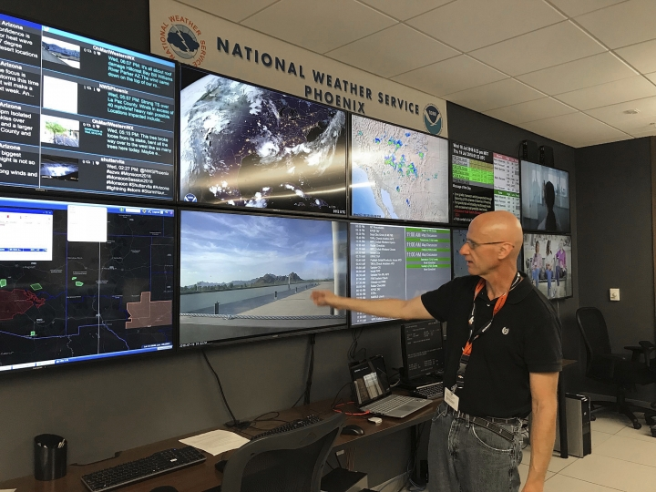 In this Wednesday, July 18, 2018 photo, National Weather Service forecaster Marvin Percha reviews monitors that track satellite and Doppler radar images, as well as his colleagues' forecasts posted on social media, at the agency's operating center in Tempe, Ariz. Percha, who grew up in the Phoenix area, says overnight low temperatures at the city's Sky Harbor International Airport have risen over time because of the effect caused by diminishing tree cover and increased development that includes vast amounts of heat-retaining asphalt and concrete. (AP Photo/Anita Snow)