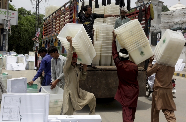 Workers collect ballot boxes and polling material after polling in Lahore, Pakistan, Thursday, July 26, 2018. The suicide attack outside the polling station in Quetta which killed dozens of people, underscored the difficulties the majority Muslim nation faces on its wobbly journey toward sustained democracy. (AP Photo/K.M. Chaudary)