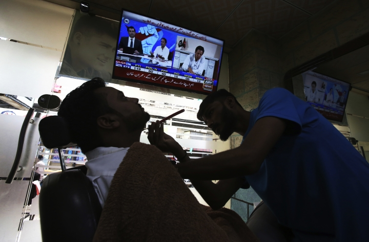 """A customer listens the speech of Pakistani politician Imran Khan, chief of Pakistan Tehreek-e-Insaf party, telecasting on news channels at a barber shop in Karachi, Pakistan, Thursday, July 26, 2018. Khan declared victory Thursday for his party in the country's general elections, promising a """"new"""" Pakistan following a vote that was marred by allegations of fraud and militant violence. (AP Photo/Fareed Khan)"""