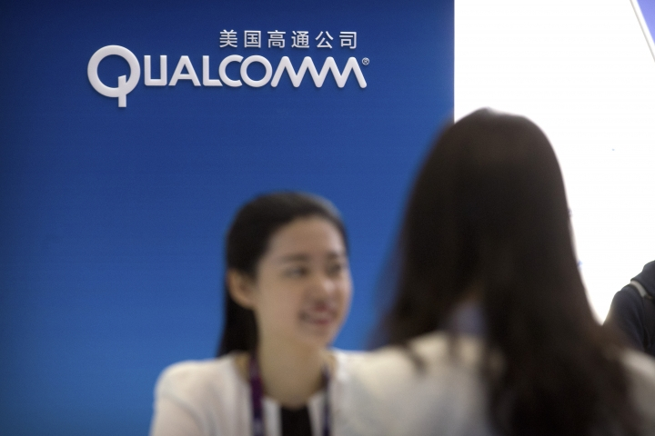 In this April 27, 2017, photo, a staff member talks with a visitor at a display booth for Qualcomm at the Global Mobile Internet Conference (GMIC) in Beijing. China's government said Friday, July 27, 2018, that tech giant Qualcomm Inc. failed to resolve anti-monopoly regulators' concerns about its proposed takeover of NXP Semiconductors in a case seen as a possible victim of U.S.-Chinese trade tensions. (AP Photo/Mark Schiefelbein)