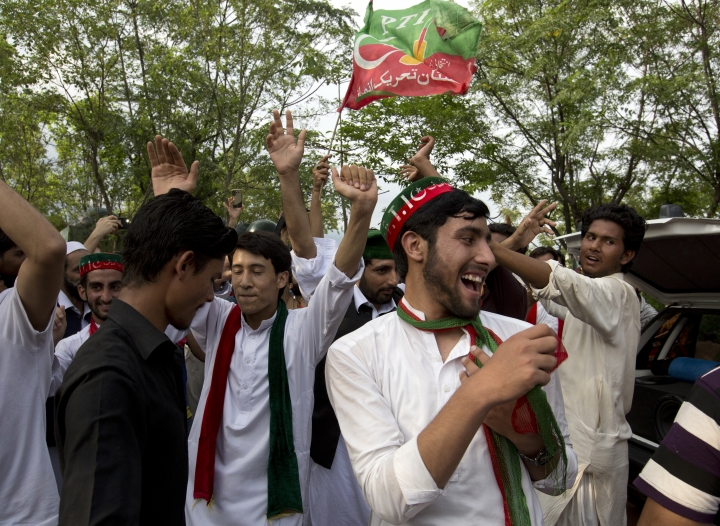 """Supporters of politician Imran Khan, chief of the Pakistan Tehreek-e-Insaf party, dance to celebrate the victory of their party candidate, outside their leader's home in Islamabad, Pakistan, Thursday, July 26, 2018. Khan declared victory Thursday for his party in the country's general elections, promising a """"new"""" Pakistan following a vote that was marred by allegations of fraud and militant violence. (AP Photo/B.K. Bangash)"""