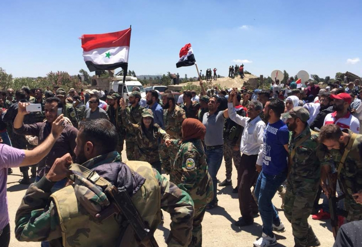 Syrian fighters and civilians hold the national flag as they celebrate the return of government authority to the southern town of Quneitra adjacent to Israeli-occupied Golan Heights, Syria, Friday, July 27, 2018. Syrian government troops recaptured the town, abandoned and largely destroyed by Israel since 1974, from armed groups who controlled it for more than four years. (AP Photo)