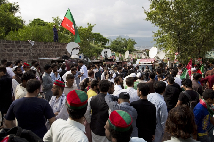 "Supporters of politician Imran Khan, chief of the Pakistan Tehreek-e-Insaf party, and media person gathered outside the Khan's residence in Islamabad, Pakistan, Thursday, July 26, 2018. Khan declared victory Thursday for his party in the country's general elections, promising a ""new"" Pakistan following a vote that was marred by allegations of fraud and militant violence. (AP Photo/B.K. Bangash)"