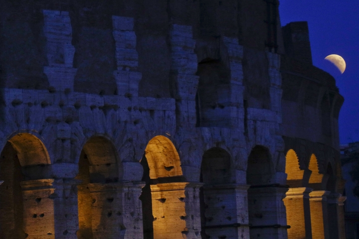 "The moon rises past the Colosseum during a complete lunar eclipse, in Rome, Friday, July 27, 2018. The so-called ""blood moon"" Friday, when it turns a deep red, will be visible at different times in Australia, Africa, Asia, Europe and South America when the sun, Earth and moon line up perfectly, casting Earth's shadow on the moon.(AP Photo/Gregorio Borgia)"