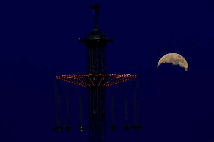 """A blood moon rises Tel Aviv, Israel, Friday, July 27, 2018. Skywatchers around much of the world are looking forward to a complete lunar eclipse that will be the longest this century. The so-called """"blood moon"""" Friday, when it turns a deep red, will be visible at different times in Australia, Africa, Asia, Europe and South America when the sun, Earth and moon line up perfectly, casting Earth's shadow on the moon. (AP Photo/Ariel Schalit)"""