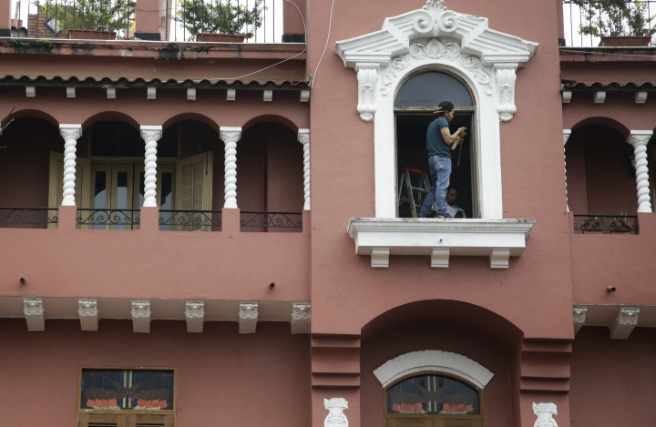 In this June 5, 2018 photo, a construction worker stands in the window at the Hotel Colombia apartment building on Plaza Bolivar in the Casco Viejo neighborhood of Panama City. Tourists and well-heeled Panamanians now stroll the paving-stone streets among gaudy hotels, fancy restaurants and trendy discos that have popped up in once-dilapidated colonial-era buildings. (AP Photo/Arnulfo Franco)