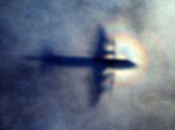 FILE - In this March 31, 2014 file photo, the shadow of a Royal New Zealand Air Force P3 Orion is seen on low level cloud while the aircraft searches for missing Malaysia Airlines Flight MH370 in the southern Indian Ocean, near the coast of Western Australia. An independent investigation report released Monday, July 30, 2018, more than four years after Malaysia Airlines Flight 370 disappeared highlighted shortcomings in the government response that exacerbated the mystery.(AP Photo/Rob Griffith, File)