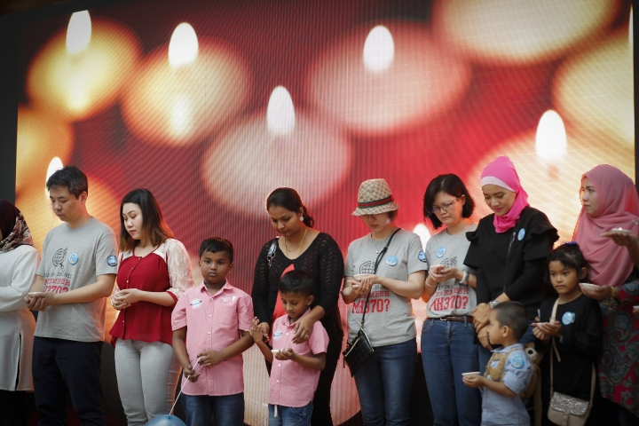 FILE - In this March 3, 2018, file photo, relative of passengers on board the missing Malaysia Airlines Flight 370 have a moment of silence during the Day of Remembrance for MH370 event in Kuala Lumpur, Malaysia. An independent investigation report released Monday, July 30, 2018, more than four years after Malaysia Airlines Flight 370 disappeared highlighted shortcomings in the government response that exacerbated the mystery. (AP Photo/Vincent Thian, File)