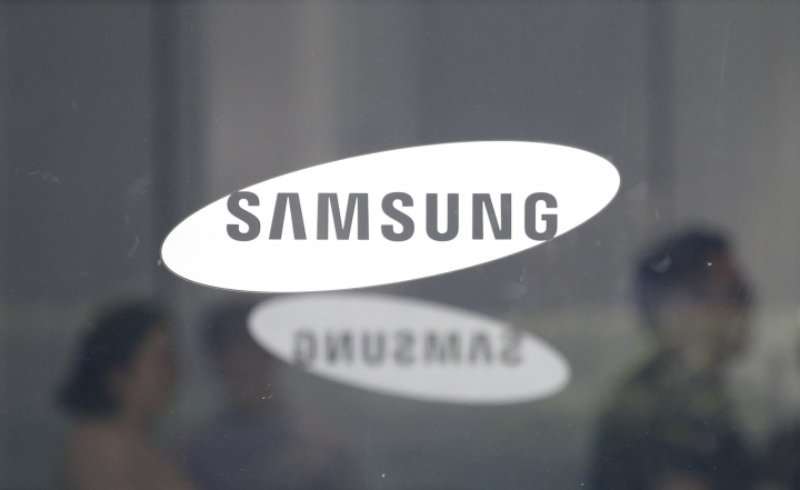 Employees walk past logos of the Samsung Electronics Co. at its office in Seoul, South Korea, Tuesday, July 31, 2018. Samsung Electronics Co. said Tuesday its second-quarter earnings rose 2 percent over a year earlier, missing expectations due to sales of smartphones and display panels that offset robust memory chip sales. (AP Photo/Ahn Young-joon)