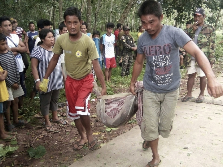 Men carry the remains of a victim in an explosion in Lamitan, Basilan province, southern Philippines on Tuesday, July 31, 2018. A soldier, five militiamen and four villagers were killed by a powerful bomb that exploded in a van the troops were inspecting Tuesday amid threats of bombings in a southern province, military officials said. (AP Photo/Christine Garcia)