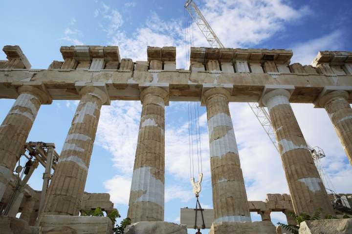 Workers raise a slab at the Parthenon temple atop of Acropolis Hill in Athens, Greece, Tuesday, July 31, 2018. Years of repair work continue at the the 2,500-year-old Parthenon temple. (AP Photo/Jon Gambrell)