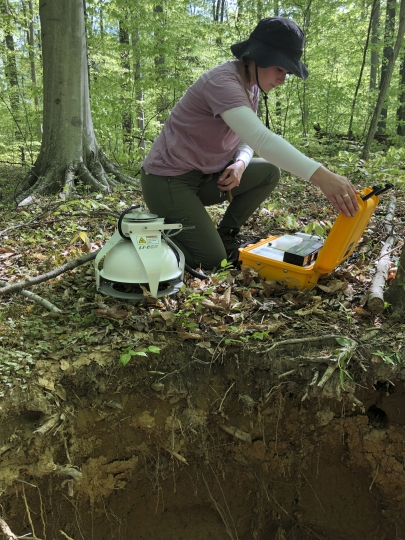This May 3, 2018 photo provided by Benjamin Bond-Lamberty shows technician Stephanie Pennington measuring the amount of carbon dioxide released into the air from the soil at the Smithsonian Environmental Research Center near Edgewater, Md. Observations from across the globe show that as temperatures have warmed, bacteria and fungi in the soil are becoming more active. These turbo-charged microbes are feeding on dead leaves and plants, releasing more heat-trapping carbon dioxide into the air, according to a study in the Wednesday, Aug. 1, 2018 edition of the journal Nature. (Benjamin Bond-Lamberty via AP)