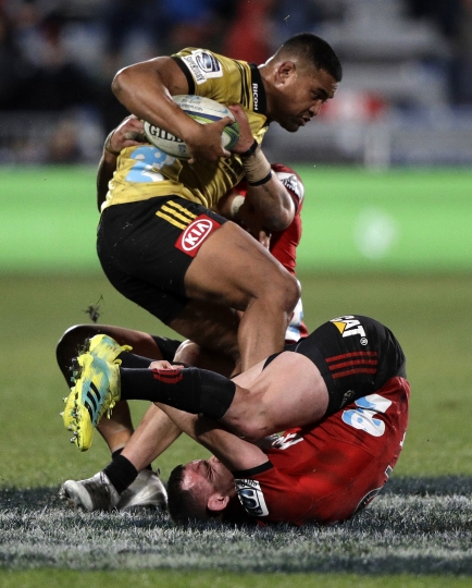 Hurricanes Julian Savea is tackled by Crusaders Ryan Crotty during their Super Rugby semifinal in Christchurch, New Zealand, Saturday, July 28, 2018. (AP Photo/Mark Baker)