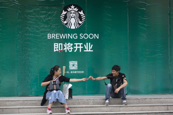 In this photo taken Wednesday, May 16, 2018, a woman hands over a watch to a man outside a Starbucks outlet under construction in Beijing, China. Starbucks and Chinese e-commerce giant Alibaba Group announced a coffee delivery venture on Thursday, Aug. 2, 2018, that adds to growing competition in China's booming delivery industry. (AP Photo/Ng Han Guan)