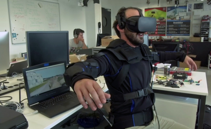 Robotics expert on the Ecole Polytechnique Federal de Lausanne, EPFL team, Matteo Macchini, displays the fly controls in a virtual reality scenario as he controls the flight of a drone, July 23, 2018, in Lausanne, Switzerland. Scientists, engineers and robotics experts at the Swiss university have teamed up to develop a jacket that allows hands-free, torso-controlled flying of drones. (Ecole Polytechnique Federale De Lausanne via AP) MANDATORY DREDIT
