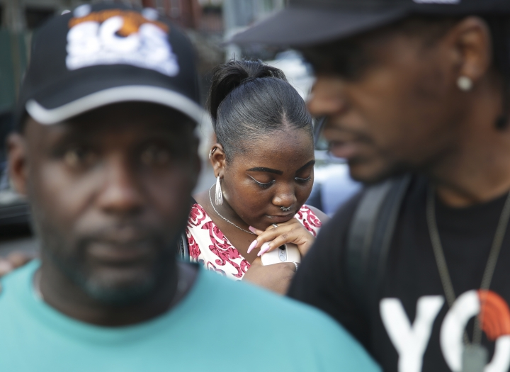 "In this July 24, 2018 photo, Alecia Armstrong bows her head during a prayer while participating in a Save Our Streets (S.O.S.) shooting response rally in Brooklyn's Bedford-Stuyvesant neighborhood in New York. S.O.S. is one of a growing number of taxpayer-financed ""violence interrupter"" groups in the nation's largest city that enlist former gang members to attack acts of violence like outbreaks of a disease that they must keep from spreading. (AP Photo/Seth Wenig)"