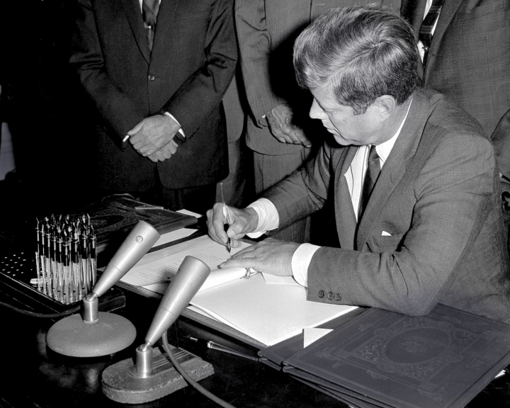 FILE - In this Oct. 7, 1963, file photo, President John F. Kennedy signs the Limited Test Ban Treaty during a ratification ceremony in the White House Treaty Room in Washington. Beginning Friday, Aug. 3, 2018, Eldred's auction gallery in East Dennis, Mass., on Cape Cod, is auctioning items associated with the late president, including pens that Kennedy used to sign the treaty. (AP Photo/File)