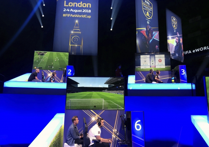 In this photo taken on Thursday, Aug. 2, 2018, competitors take part in the eWorld Cup grand final in London. Three weeks after the World Cup finished in Russia, the finals of the e-sports version are taking place in London, with gamers being tested for performance-enhancing substances for the first time by FIFA. It's a sign of the increasing professionalization of the gaming version of the World Cup, with the winner collecting $250,000. (AP Photo/Rob Harris)
