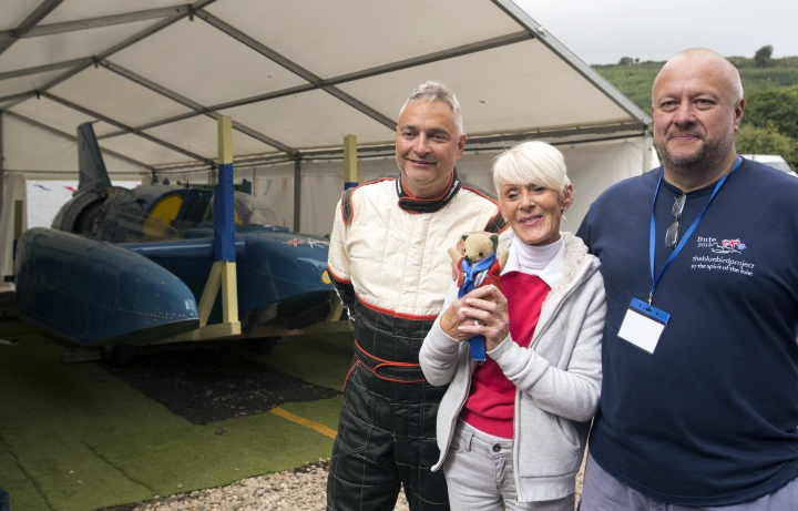 Hydroplane Pilot Ted Walsh, left, Gina Campbell the daughter of pilot Donald Campbell and engineer Bill Smith pose for a photo with the restored Bluebird K7 before it takes to the water for the first time in more than 50 years off the Isle of Bute on the west coast of Scotland, Saturday Aug. 4, 2018. The famed jet boat Bluebird has returned to the water for the first time since a 1967 crash that killed pilot Donald Campbell during a world speed-record attempt. Watched by Campbell's daughter Gina Campbell, the restored Bluebird was lowered Saturday into Loch Fad on Scotland's Isle of Bute, where it will undergo low-speed tests.(David Cheskin/PA via AP)