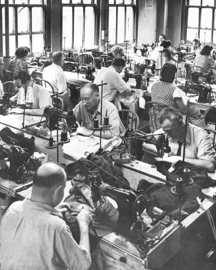 FILE - In this June 28, 1944, file photo, garment workers sew clothing at a loft factory in New York. Hundreds of thousands of garment workers once toiled in the sweaty, elbow-to-elbow workshops of midtown Manhattan before the whirring of sewing machines was mostly silenced by foreign competition. But a group of New Yorkers - manufacturers, landlords, designers, politicians - want to preserve some of the bustling sewing scene by zoning the neighborhood for at least 300,000 square feet of garment workshops now serving higher-end designers. (AP Photo/File)