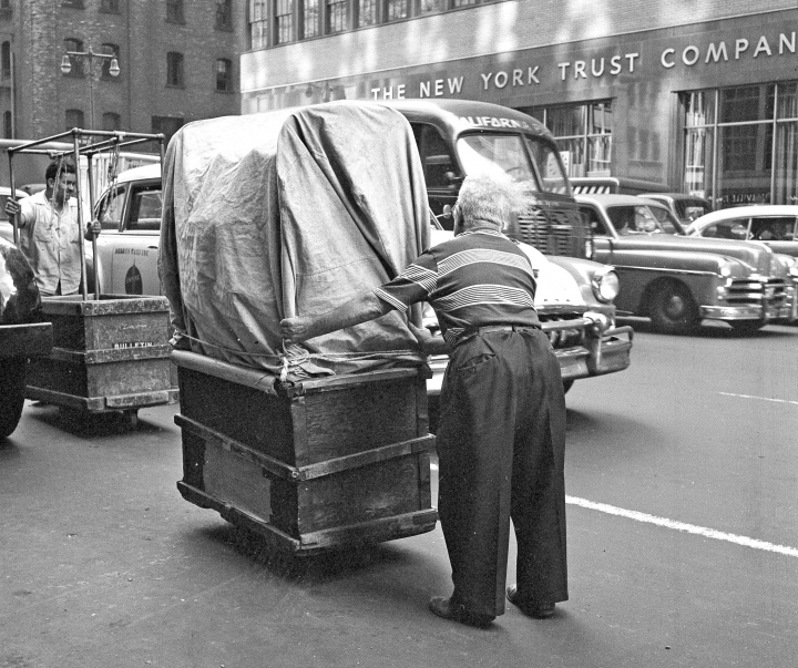 FILE - In this Aug. 26, 1958, file photo, a worker pushes a wheeled container of newly made women's wear through the streets on New York's Garment District. Hundreds of thousands of garment workers once toiled in the sweaty, elbow-to-elbow workshops of midtown Manhattan before the whirring of sewing machines was mostly silenced by foreign competition. But a group of New Yorkers - manufacturers, landlords, designers, politicians - want to preserve some of the bustling sewing scene by zoning the neighborhood for at least 300,000 square feet of garment workshops now serving higher-end designers. (AP Photo/Dan Grossi, File)