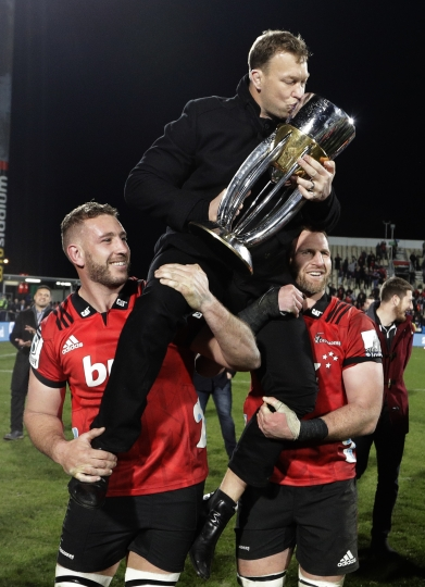 Crusaders player's Luke Ramano, left, and Kieran Read hold retiring teammate Wyatt Crockett aloft as they celebrate after defeating the Lions 37-18 to win Super Rugby final in Christchurch, New Zealand, Saturday, Aug. 4, 2018. (AP Photo/Mark Baker)